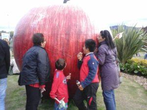 Familia disfrutando de una manzana gigante en una granja