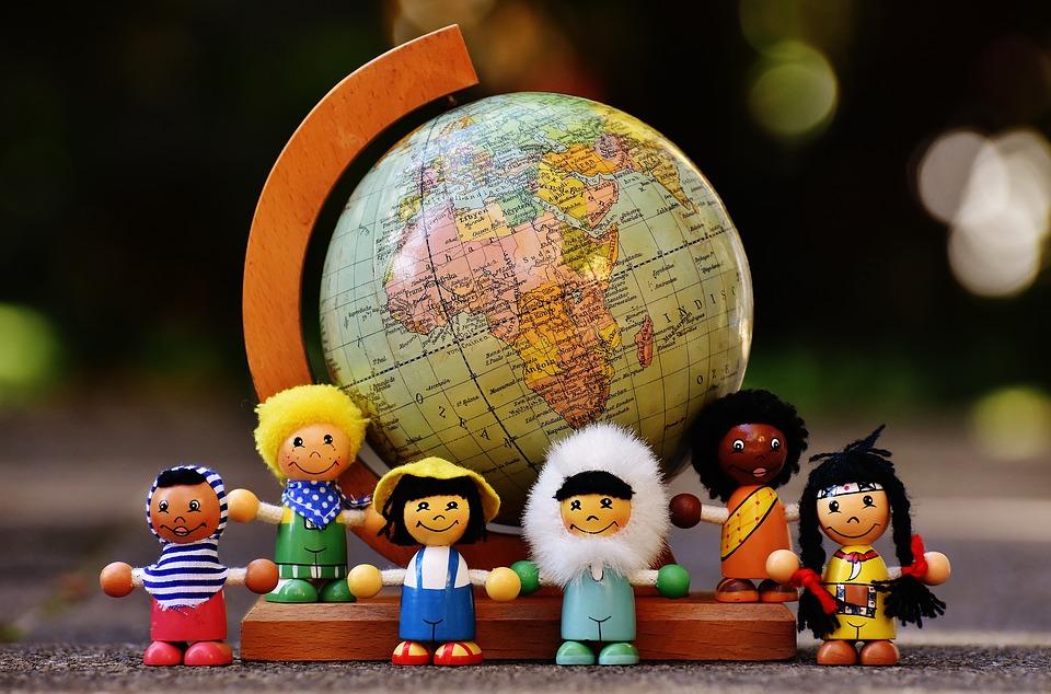 Muñecos de diferentes nacionalidades y un mapa mundi pixabay