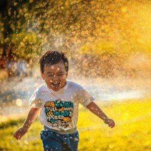 Niño disfrutando de la lluvia unsplash